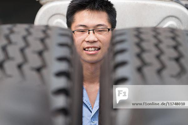 Kopfporträt eines männlichen Fabrikarbeiters zwischen LKW-Reifen in einer Kranfabrik  China