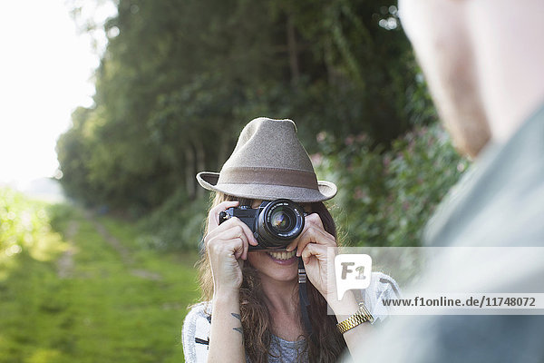 Over the shoulder view of young woman photographing boyfriend in field