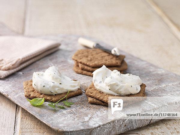 Knoblauch-Kräuter-Weichkäse auf sechseckigen Crackern auf weiß getünchtem Schneidebrett