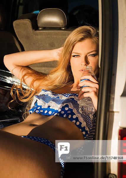 Junge Frau auf dem Rücksitz eines Autos liegend  aus einer Wasserflasche trinkend  Porträt