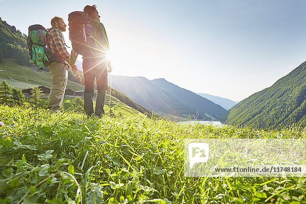 Young hiking couple looking out over Vernagt reservoir and Finailhof farmhouse  Val Senales  South Tyrol  Italy