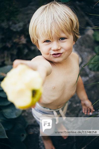 Hochwinkelaufnahme eines blonden Jungen  der einen Apfel hält und lächelnd in die Kamera schaut  Bludenz  Vorarlberg  Österreich Hochwinkelaufnahme eines blonden Jungen, der einen Apfel hält und lächelnd in die Kamera schaut, Bludenz, Vorarlberg, Österreich