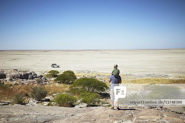 Father and son enjoying view  Kubu Island  Makgadikgadi Pan  Botswana  Africa
