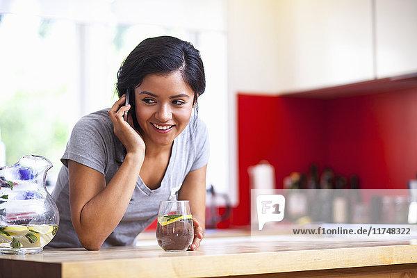 Junge Frau benutzt Mobiltelefon in der Küche