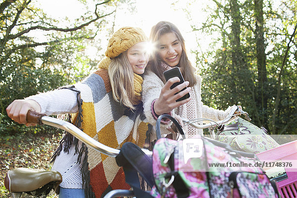 Teenage girls in forest holding bicycles using smartphone to take selfie smiling