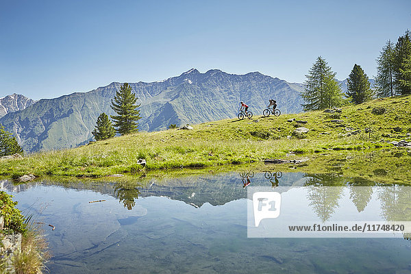 Young couple mountainbiking down hill  Karthaus  Val Senales  South Tyrol  Italy