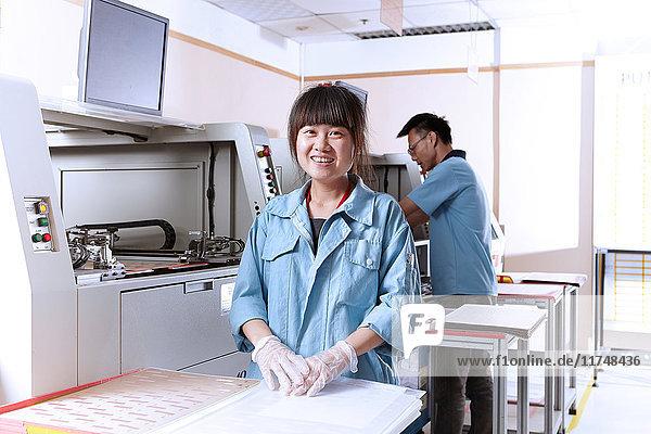 Junge Frau in flexibler Elektronikfabrik schaut lächelnd in die Kamera