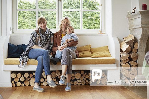 Erwachsene Frauen sitzen auf einem Fensterplatz mit einem Jungen auf dem Schoß