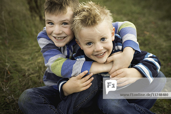 Cropped view of boys sitting on grass hugging  looking at camera smiling