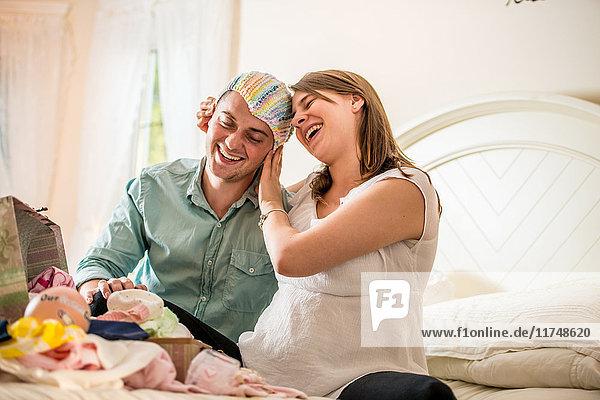 Ehepaar durchsucht Kiste mit Babykleidung
