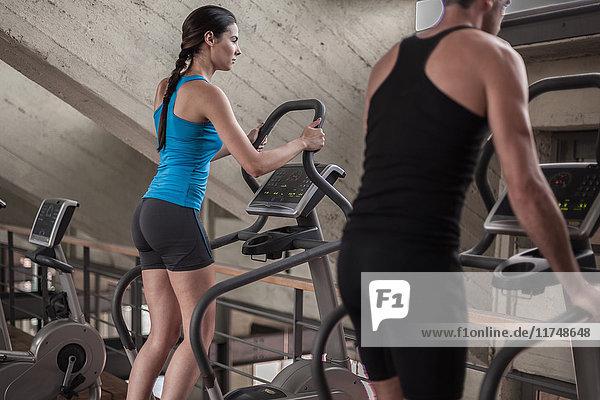 Mann und Frau benutzen Fitnessgeräte