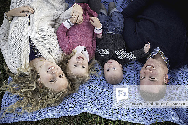 Overhead portrait of mid adult couple on picnic blanket with daughter and baby boy