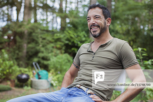 Portrait of mature man sitting in garden