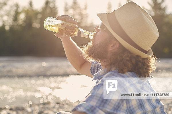 Seitenansicht eines mittleren erwachsenen Mannes mit Hut  der Bier aus einer Bierflasche trinkt