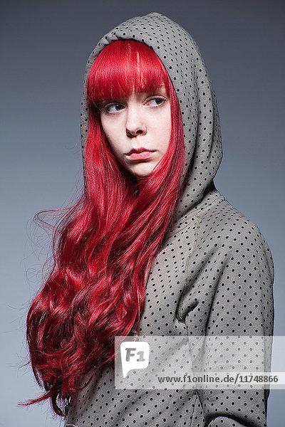 Junge Frau mit langen roten Haaren in Kapuzen-Oberteil
