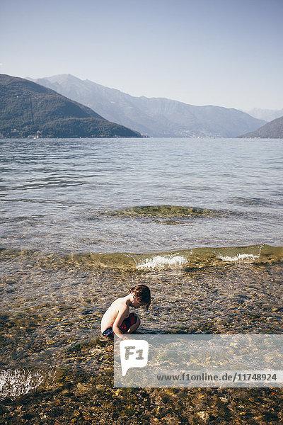 Seitenansicht eines Jungen  der im seichten Wasser kauert und auf eine Bergkette blickt  Luino  Lombardei  Italien