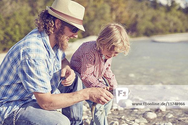 Mittelgroßer erwachsener Mann und Junge neben dem Fluss bei der Untersuchung von Fischen  die an der Angelschnur befestigt sind