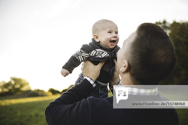 Mid adult man holding up baby son in field