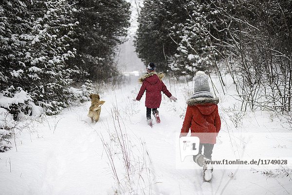 Sisters exploring snowy forest with dog