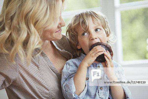 Kleiner Junge sitzt auf einem Schokoladenmuffin  während seine Mutter zuschaut