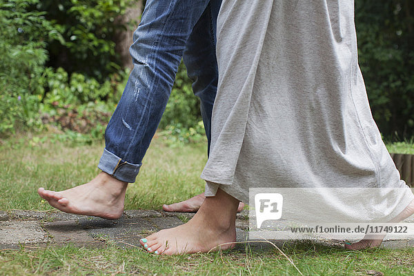Couple wearing skinny jeans and maxi dress walking barefoot in garden