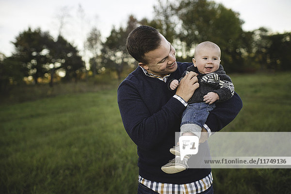 Mid adult man carrying baby son in field