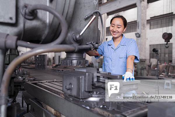 Female factory worker working on machine in crane factory  China