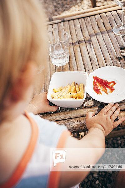 Über-die-Schulter-Ansicht eines Jungen  der Pommes Frites und Ketchup isst