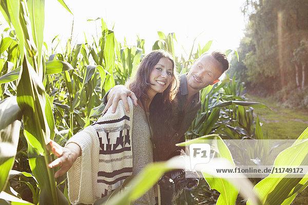 Couple amongst corn plants in field
