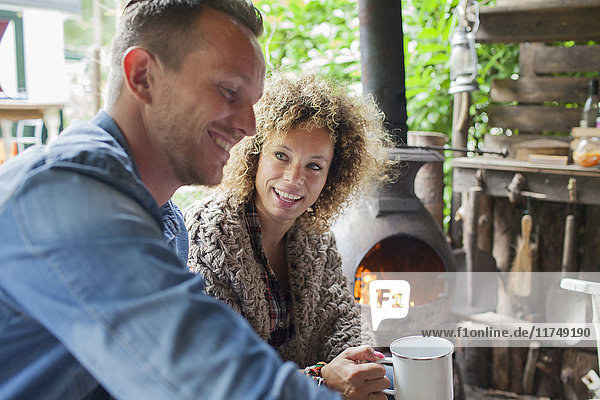 Mid adult couple drinking coffee in open cabin with wood stove