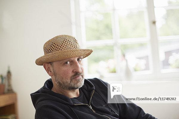 Porträt eines reifen erwachsenen Mannes mit Strohhut  der in die Kamera schaut