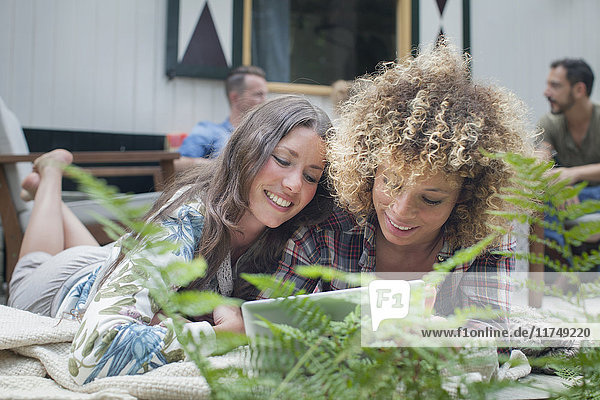 Two female friends browsing digital tablet on cabin porch