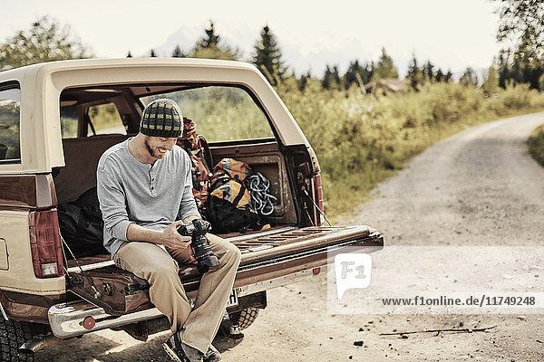 Junger Mann sitzt auf der Ladefläche eines Pickup-Trucks und hält Kamera