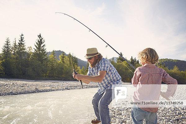 Mittelgroßer erwachsener Mann und Junge am Fluss  die mit der Angelrute Fische fangen