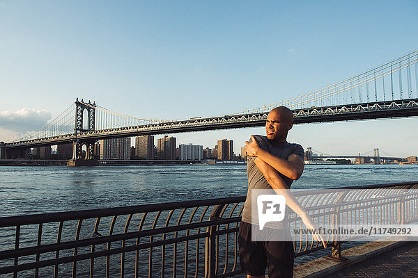 Young male runner stretching in front of Manhattan bridge  New York  USA