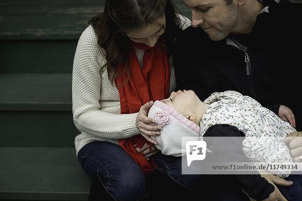 Mutter und Vater sitzen mit ihrer kleinen Tochter im Freien