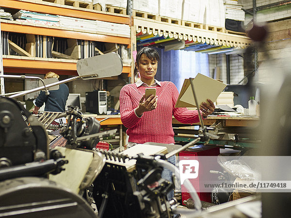 Mid adult woman reading smartphone text in traditional print workshop