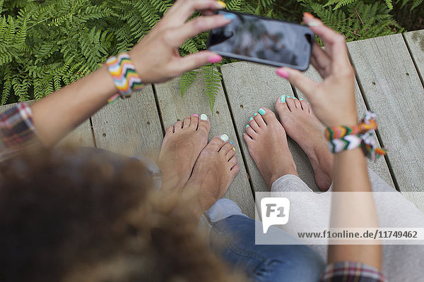 Two women photographing painted toenails on cabin porch