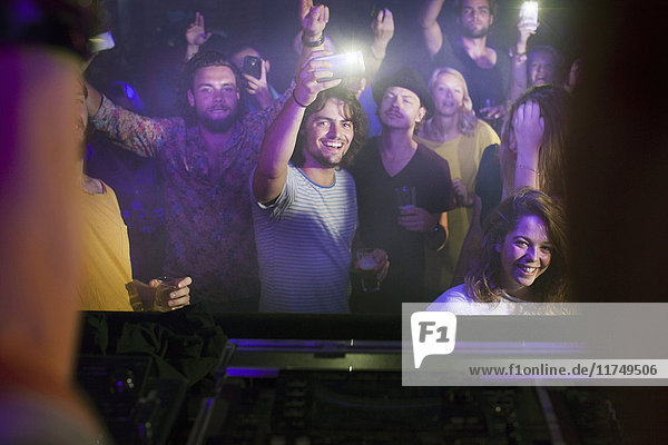 Group of friends watching and taking photograph of performer in club