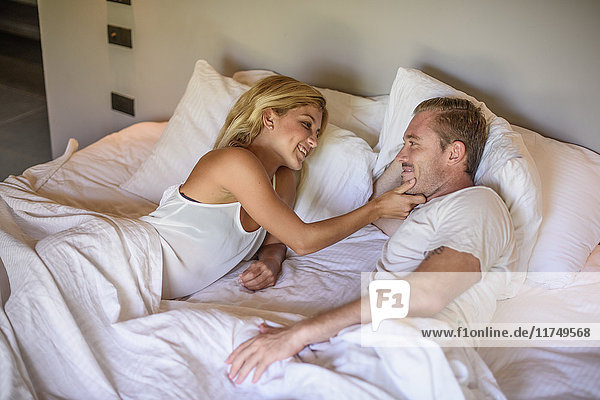 Junge Frau berührt Freundinnen im Bett am Kinn