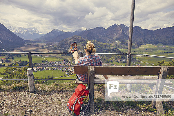 Mature woman sitting on bench  looking at mountain view  Garmisch-Partenkirchen  Bavaria  Germany