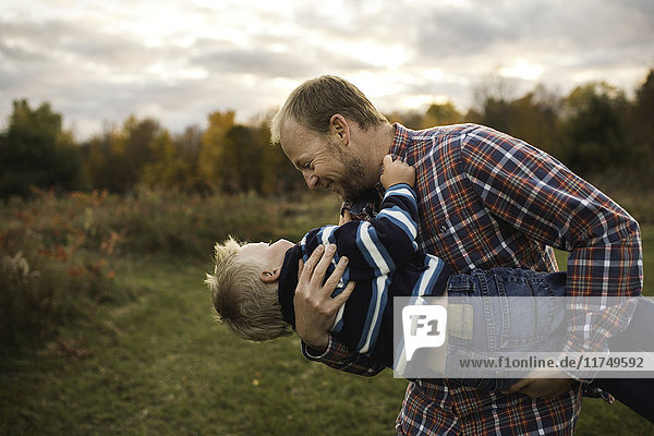 Father carrying son in arms playfully  face to face smiling