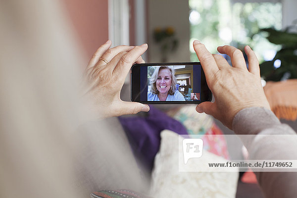 Senior woman  holding smartphone  on video call with friend