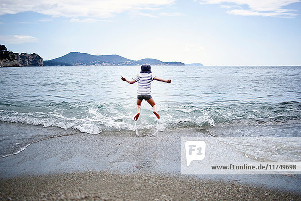 Little boy jumping into the sea