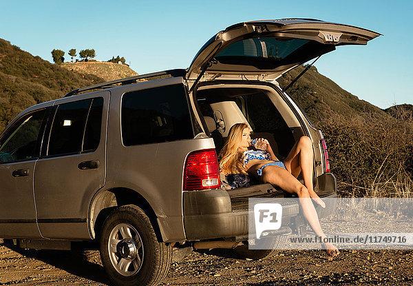 Junge Frau auf dem Rücksitz eines Autos liegend