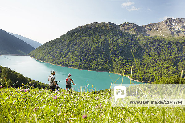 Young couple on mountain bikes looking out at Vernagt reservoir  Val Senales  South Tyrol  Italy