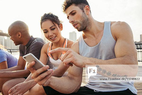 Junge Erwachsene laufen mit Freunden über den Touchscreen eines Smartphones am Flussufer  New York  USA
