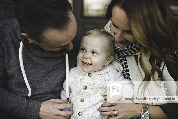 Couple holding baby boy looking down smiling