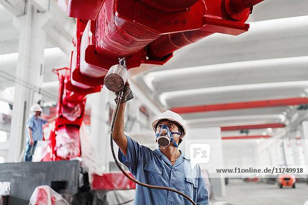 Männliche Arbeiter sprühen einen Kranarm in einer Fabrikhalle rot an  China