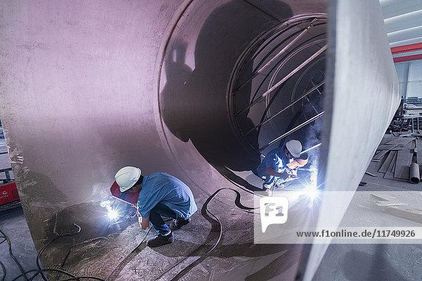 Zwei männliche Schweißer arbeiten in einem Industrierohr in einer Kranfabrik  China